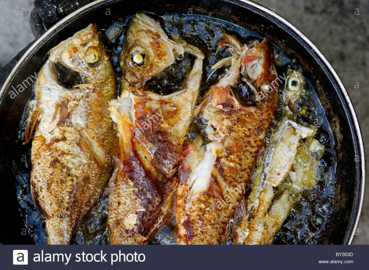 Fried fish frying in a pan filled with cooking oil Mozambique ...