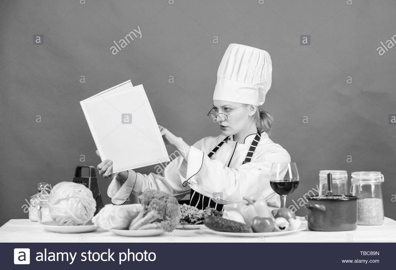 Woman chef cooking healthy food. Girl read book top best culinary ..